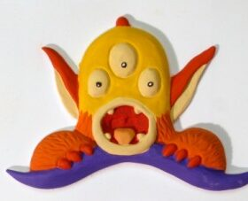 A yellow three-eyed, scared little monster peeps over the top of his purple duvet.