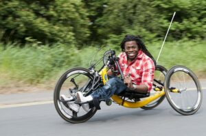 Ade Adepitan, smiling, speeding along the road in a three-wheeled racing wheelchair.