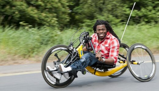 Ade Adepitan in a racing wheelchair speeding down a road smiling.