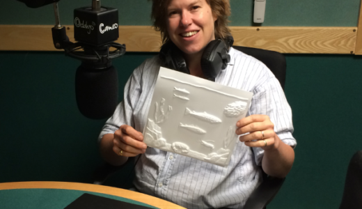 Allegra McEvedy in the studio wearing headphones, sitting in front of a microphone and holding up a tactile picture.