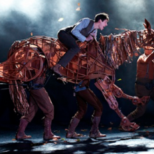 Albert and Joey go for a run, a photo from the stage production of Warhorse, a life size puppet horse running with a boy on his back.