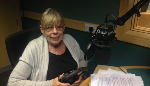 Frances de la Tour in studio holding a pair of headphones, smiling, in front of a microphone.