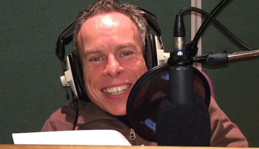 Warwick Davis in the studio reading for our Film book, wearing headphones and sitting in front of a microphone.
