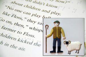 Tactile picture of a farmer from Floss, with braille and text page in background.