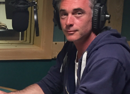Greg Wise close up shot,, holding a script and looking at the camera whilst in studio.