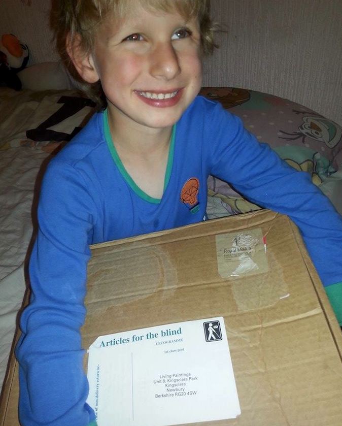 Fred smiling and holding a brown box  postal delivery from Living Paintings