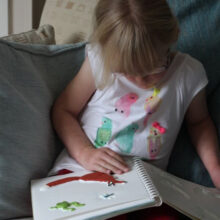 Abi reading Nine Ducks Nine on the sofa.