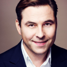 David Walliams head and shoulders shot, clean shaven and smiling, wearing a suit.