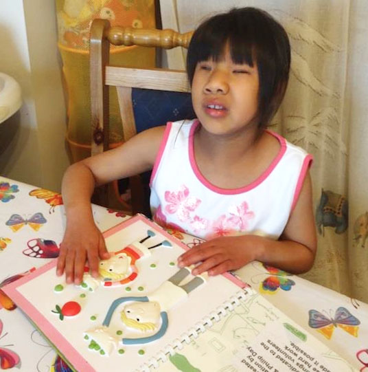 Living Paintings library member reading touch to see book, Charlie and Lola