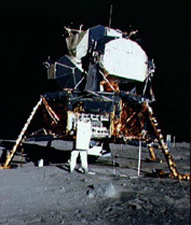 Apollo 11 Lunar lander on the moon, colour photograph with astronaut in the foreground.
