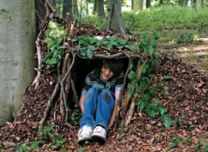 A boy smiling and sitting in a forest den made of leaves and twigs.