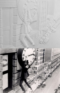 Safety last tactile image showing a man in a straw hat and suit hanging from the hands on a clock face high above a busy road.