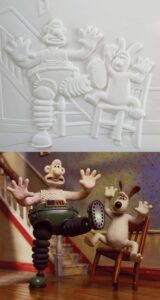 Wallace and Gromit tactile image showing Wallace wearing robotic legs and Gromit falling off his chair.