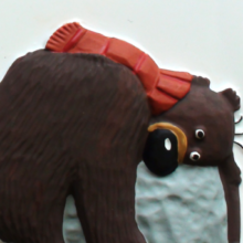Hugless Douglas wearing a red scarf and hugging a rock.