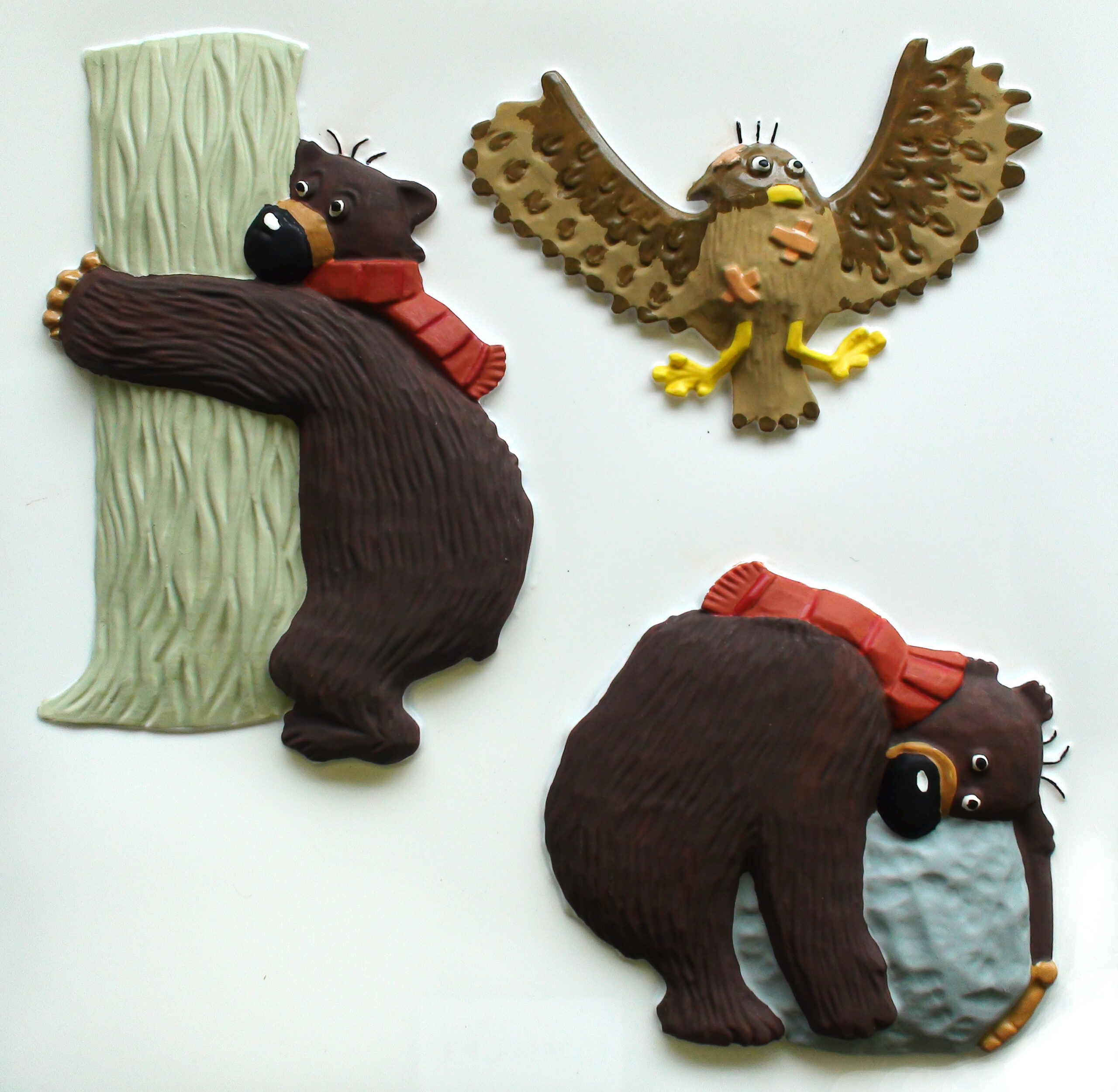 Hugless Douglas tactile pictures, showing him hugging a tree, a rock and an owl in flight.