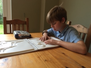 Freddy testing our bushcraft touch to see book on his kitchen table.