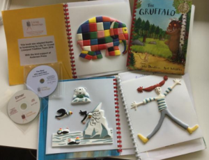 A display of tactile and audio books showing open books, CD and tactile pictures including Elmer elephant and a happy girl.