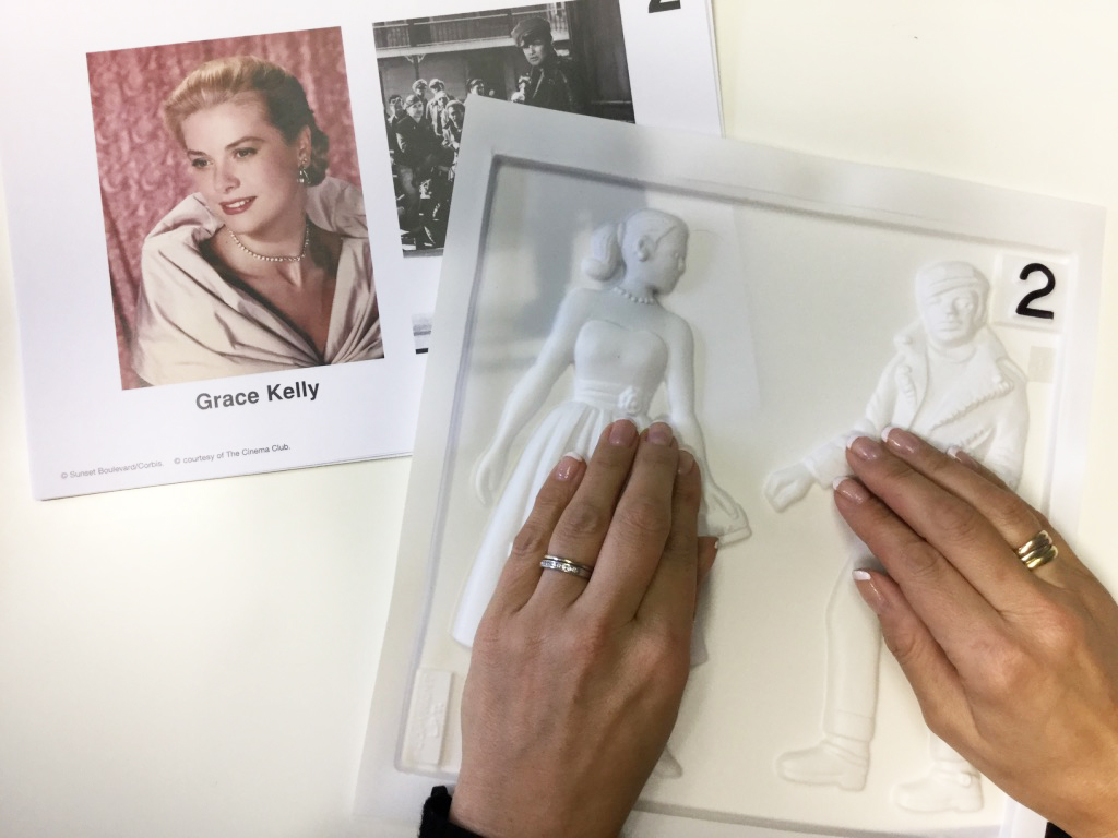 Hands feeling a tactile picture of Grace Kelly, wearing a sweetheart neckline dress.