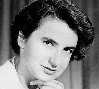 Head shot, black and white, of a woman with her hand to her chin looking at the camera.
