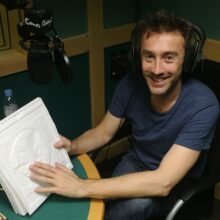 Dallas Campbell studio wearing headphones holding a tactile picture and smiling.
