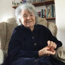 Book Club member Joy, smiling, sitting in her arm chair.