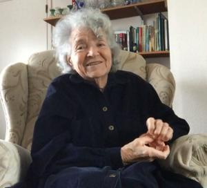 Book Club member Joy, smiling, sitting in an armchair.