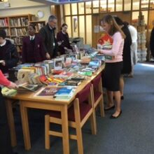 School library bookstall with books on tables in a library.