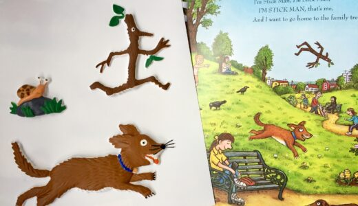 Stick Man book open on the park page with a tactile picture of Stick Man and the dog and the snail.