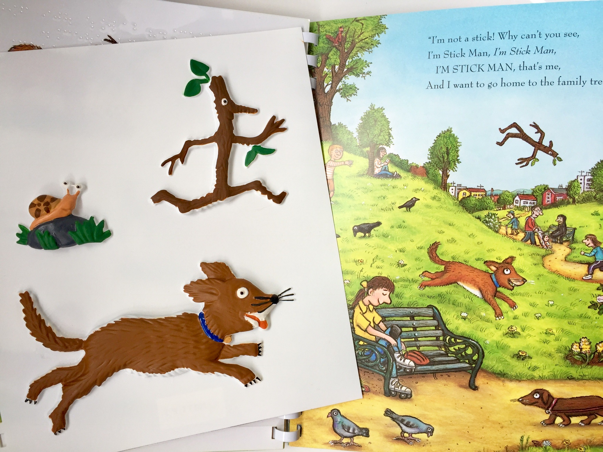 Stick Man book open on the park page with a tactile picture of Stick Man and the dog and the snail