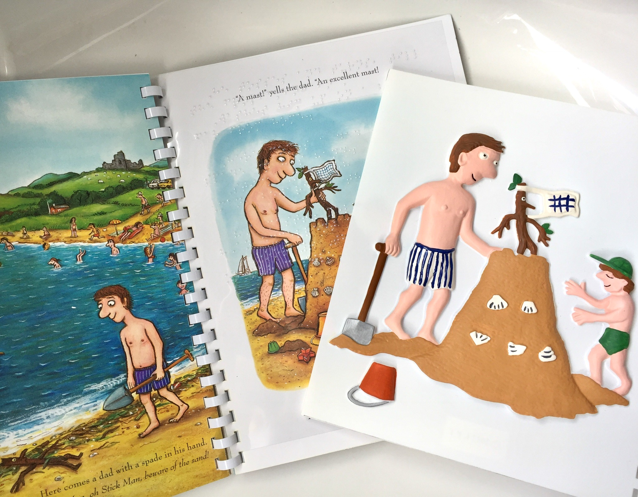 Stick Man book open on the beach pages with a tactile picture of the man and the sandcastle on top