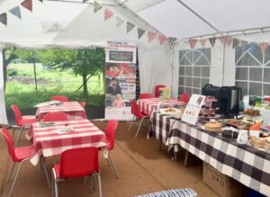 Inside the marquee. Checked tablecloths and colourful bunting.