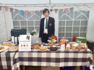 Volunteer Jacob helping out behind the cake stall