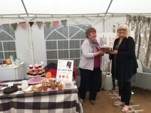 Volunteer Stevie offering a cake to Living Paintings CEO Camilla Oldland