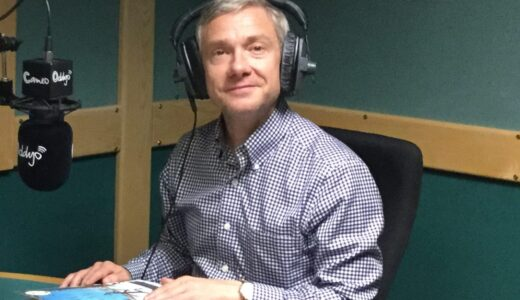 Martin Freeman in the studio recording audio for Stick Man, sitting as a desk wearing headphones.