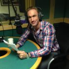 Dr Christian Jessen in studio, holding a script and smiling.