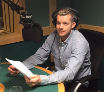 Russell Tovey in the studio, headphones on in front of microphone and holding a script.