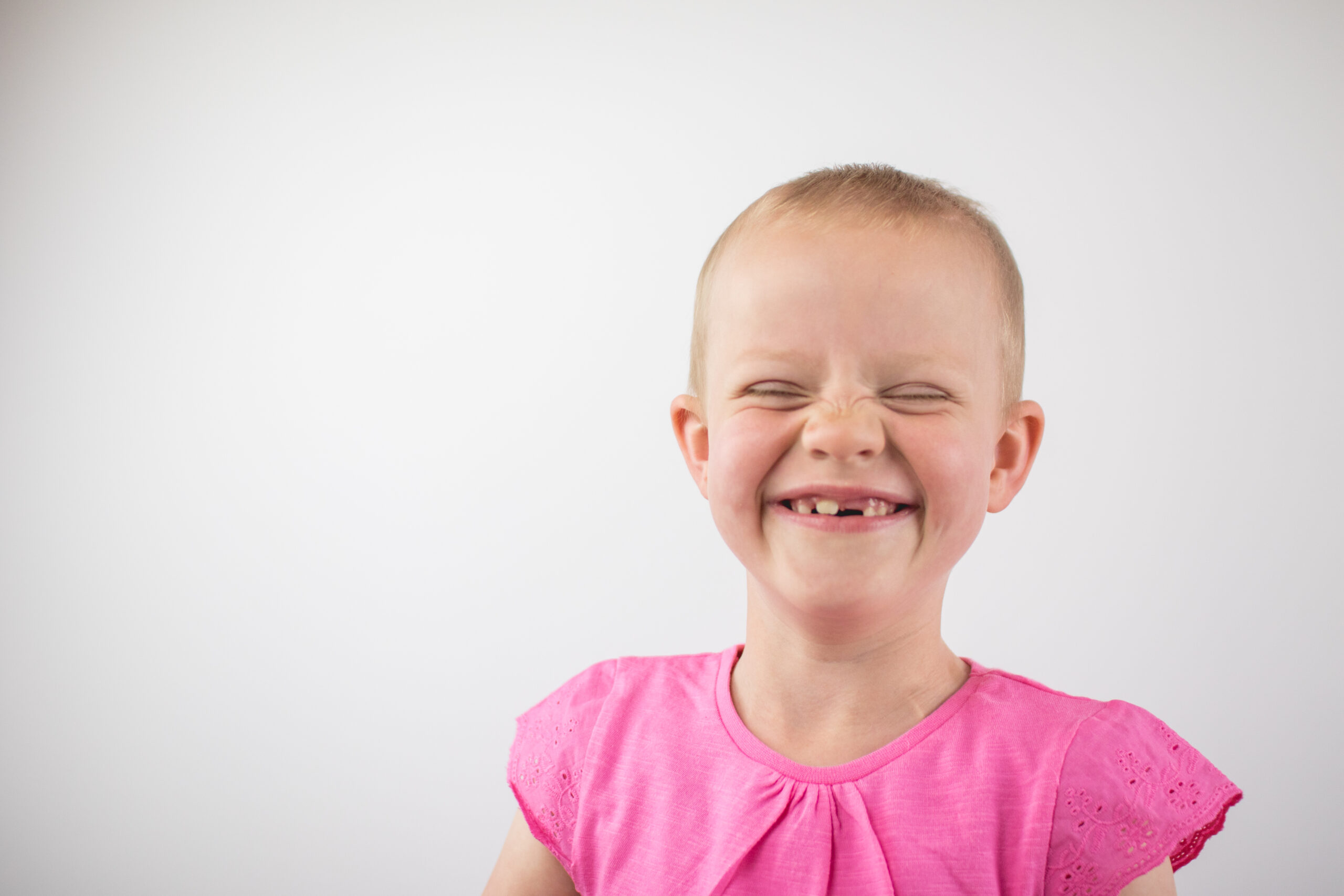 A picture of one of our young beneficiaries Tayen smiling with her eyes closed. She's wearing a pink t-shirt.