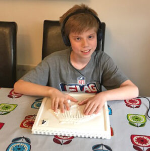 One of our young beneficiaries, Freddy reading our Touch to See WWII book, sitting at a table.