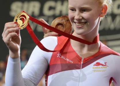 Sophie Thornhill, smiling, holding up a gold medal on a red ribbon.