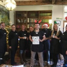 A team of Nationwide volunteers who waitered at the event. They're all wearing black t-shirts and aprons, and three have festive headwear.
