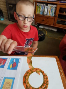 Library member doing the paper snake experiment, holding a ruler attached by static to a tissue paper snake.