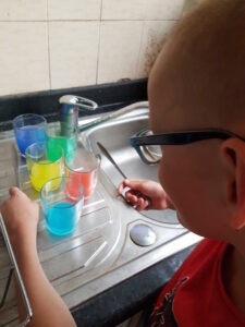 Library member doing the tap out a tune experiment with glasses filled with different amounts of coloured water.