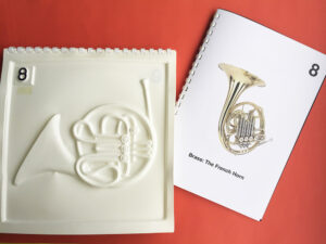 Tactile picture and colour pamphlet with a photo of a French Horn.