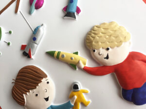Two  boys each holding a toy, a rocket and an astronaut.