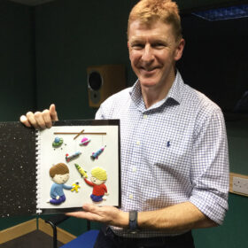 Tim Peake holding up Goodnight Spaceman tactile book and smiling