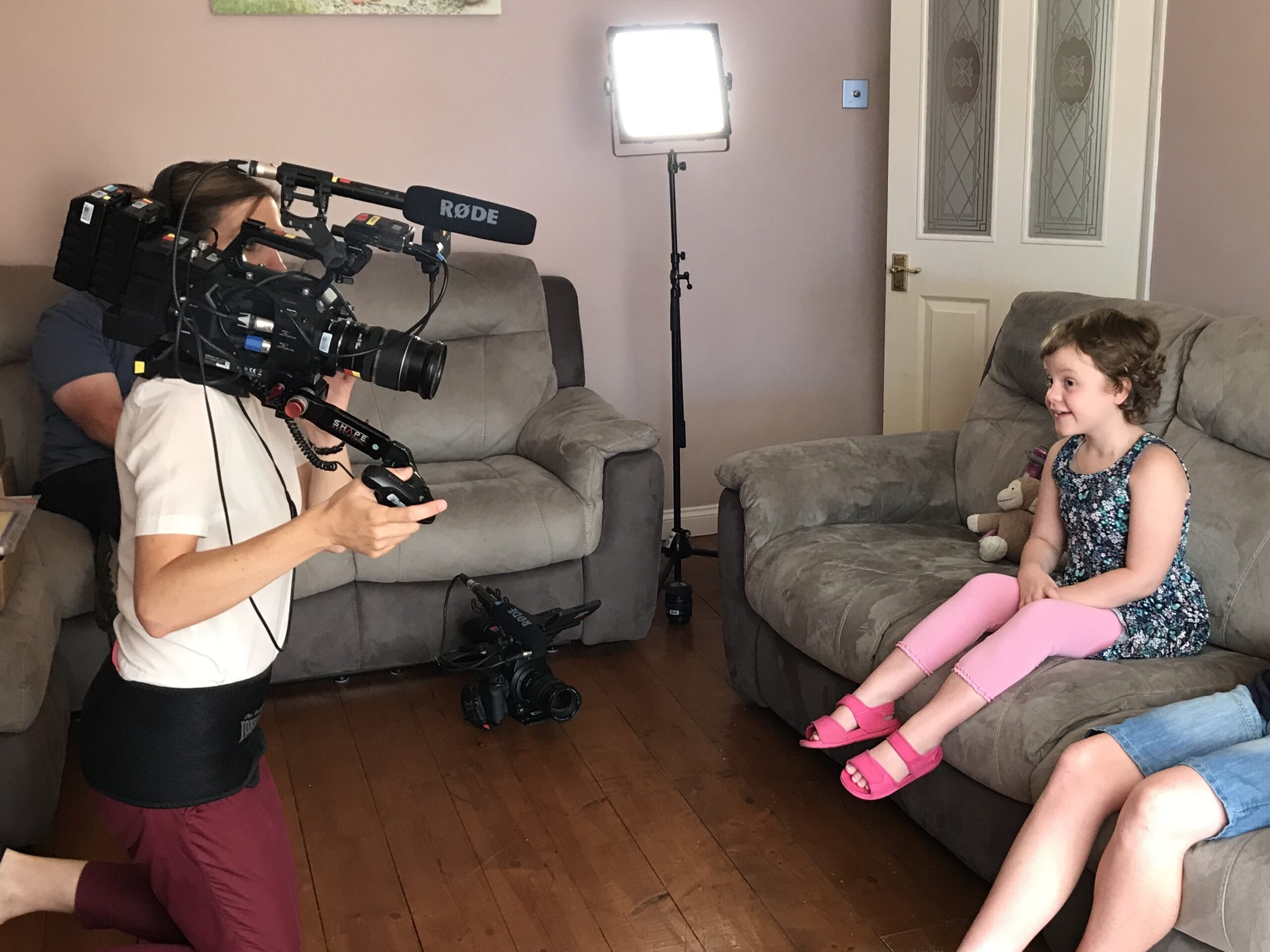 Young library member Tayen being filmed for the Lifeline appeal, sitting on her sofa with the film camera pointing at her.