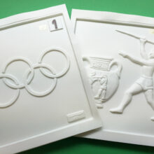 Olympic ring and a Greek athlete throwing a javelin