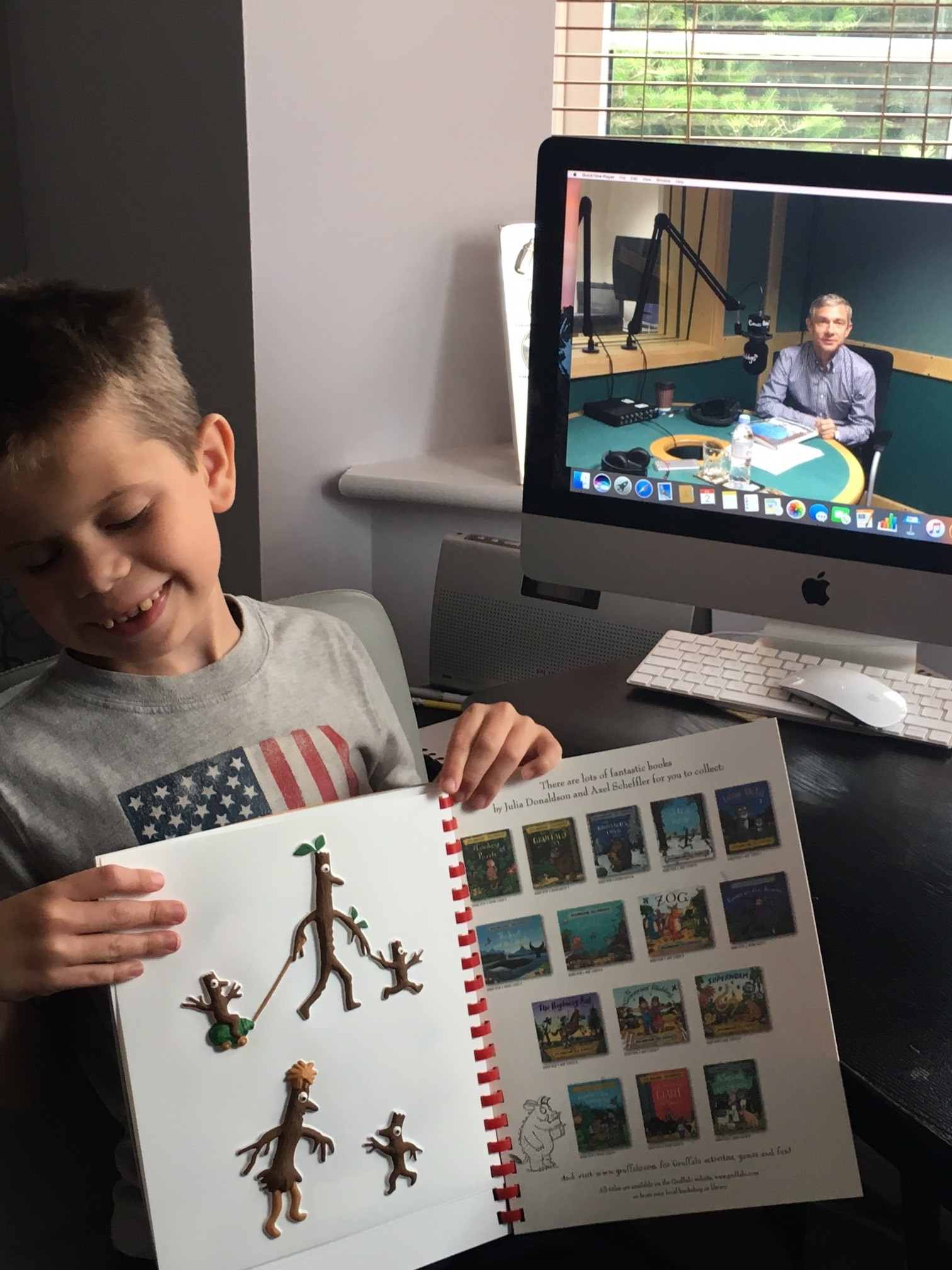Young library member Ted holding up a tactile copy of Stick Man by Julia Donaldson