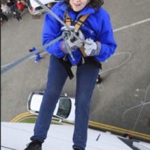 A woman abseiling down a tall building.