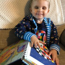Young boy smiling while sitting on a sofa and exploring a tactile image of Elmer the elephant with his fingers
